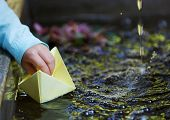 picture of wet pants  - Little four year old boy in a blue outfit playing with paper boats in a small outdoor water fountain