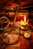 Vintage magnifying glass, compass, pocket watch, spyglass lie on an old ancient map with a lit candl