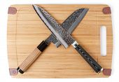 Pair of japanese knives on wooden cutting board