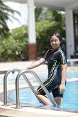 foto of ten years old  - ten years old girl playing in swimming pool wearing swimming suit - JPG