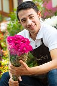 Friendly Asian florist or seller in a flower shop holding a flower bouquet