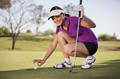 image of cheating  - Beautiful young woman trying to cheat at golf - JPG
