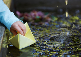 stock photo of wet pants  - Little four year old boy in a blue outfit playing with paper boats in a small outdoor water fountain