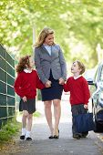 Mother Walking To School With Children On Way To Work