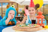Boy in costumes of monsters and girl in festive cap having fun in a cafe with pizza