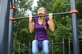 Young beautiful girl doing chin-ups on the outdoor sports ground