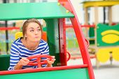 Funny girl sitting in a toy car on the playground and imitates driving a car