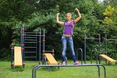 Beautiful girl standing on the parallel bars at sports ground and showing her biceps