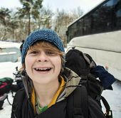 teenager with backpack on a winter trip in snow