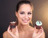Portrait of beautiful young girl with chocolate cupcake on brown background