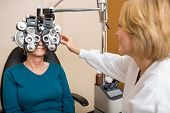 Female optician examining senior patient's vision with phoropter