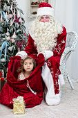 little girl looks out of a bag with Santa Nicolai's gifts