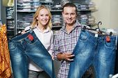 Young couple choosing jeans during clothing shopping at sales store