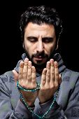 stock photo of tasbih  - Western Muslim with Sweatshirt Praying with Tasbih - JPG