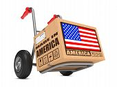 stock photo of free-trade  - Cardboard Box with Flag of USA and Made in America Slogan on Hand Truck White Background - JPG