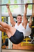 Smiling Young Man Hanging From Gym Equipment