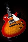 stock photo of lp  - Cherry sunburst LP guitar on dark brown wooden floor