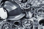 industrial hardhat set against gears, cogs and ball-bearings