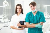 Portrait of happy young doctor and female assistant with clipboard in dental clinic