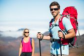 Man and woman hiking on beautiful mountain trail. Trekking and backpacking in the mountains. Healthy lifestyle outdoor adventure concept.