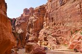 PETRA, JORDAN - MARCH 15, 2014: Tourists walks in the Siq, the canyon of ancient Petra. Since 1985, Petra is listed as UNESCO World Heritage site