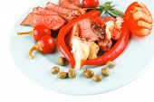 bacon meat slices served with tomatoes capers and red hot chili peppers on blue plate isolated on wh