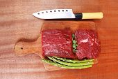 red fresh raw beef veal fillet with asparagus and stainless steel chef knife on cutting plate over w
