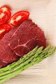 foto of flank steak  - fresh raw beef meat steak fillet on wooden plate with asparagus and tomatoes ready to prepare - JPG