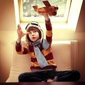 Little boy aviator dreaming and playing with wooden handmade toy plane at home, vintage toned