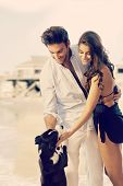 stock photo of caress  - Young casual caucasian dream couple caressing dog at summer beach - JPG