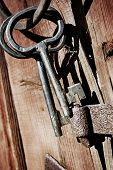 old antique 17th century keys hanging on old wooden barn-wall