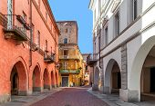 Narrow paved street between old medieval and renewed buildings in town of Alba in Piedmont, Northern Italy.