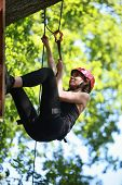 Attractive woman climbing in adventure rope park in safety equipment
