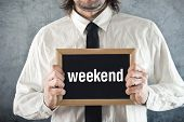 Businessman Holding Blackboard With Weekend Title