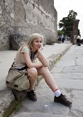 Italy. Pompeii. The woman the tourist has a rest on the street of the destroyed city