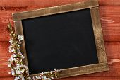 image of dainty  - Old blank vintage school slate or chalkboard lying on an old rustic wooden background with dainty white flowers in two corners ready for your text or message - JPG