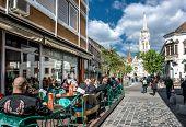 Tourists Sitting In A Sidewalk Cafe Near Matthias Church