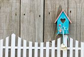 Teal blue birdhouse with wooden hearts hanging over white picket fence