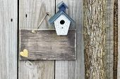 Blank wood sign with antique blue and white birdhouse next to tree