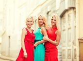 holidays and tourism, friends, hen party and blonde girls concept - three beautiful women in the city
