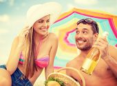 summer, holidays, vacation and happy people concept - smiling couple having picnic on the beach under colorful umbrella