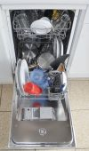 Dishwasher with open hatch and clean dinnerware