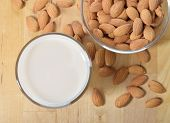 picture of substitutes  - Almond milk as a substitute for dairy milk. Glass of almond milk and almonds on a wooden table.