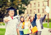 education, campus and teenage concept - smiling teenage boy in corner-cap with diploma and classmates on the back