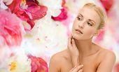 beauty and spa concept - face of beautiful woman touching her face skin