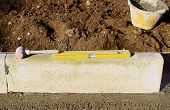 plastic hammer and spirit level on newly installed curb