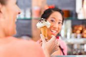 Young female customer and saleswoman in an ice cream parlor with ice cream cornet