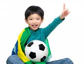 Little boy holding soccer ball with Brazil flag