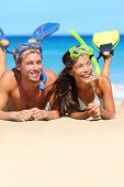 Beach couple having fun snorkeling on vacation. Happy young multiracial couple lying on summer beach