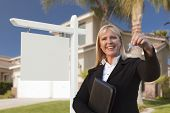 Female Real Estate Agent Handing Over the House Keys in Front of a Beautiful New Home and Blank Real Estate Sign.